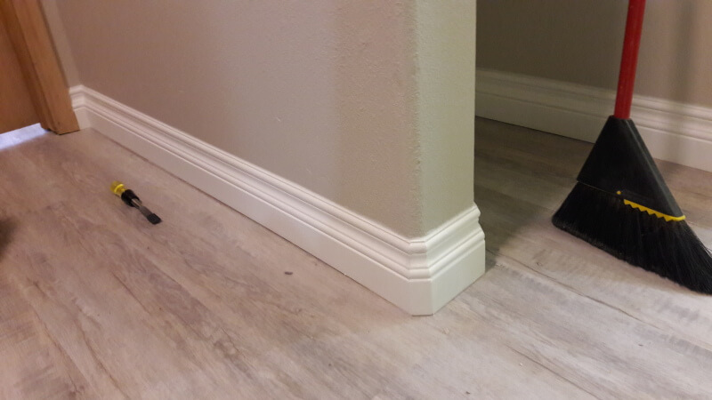 Baseboard trim installed on new vinly plank flooring